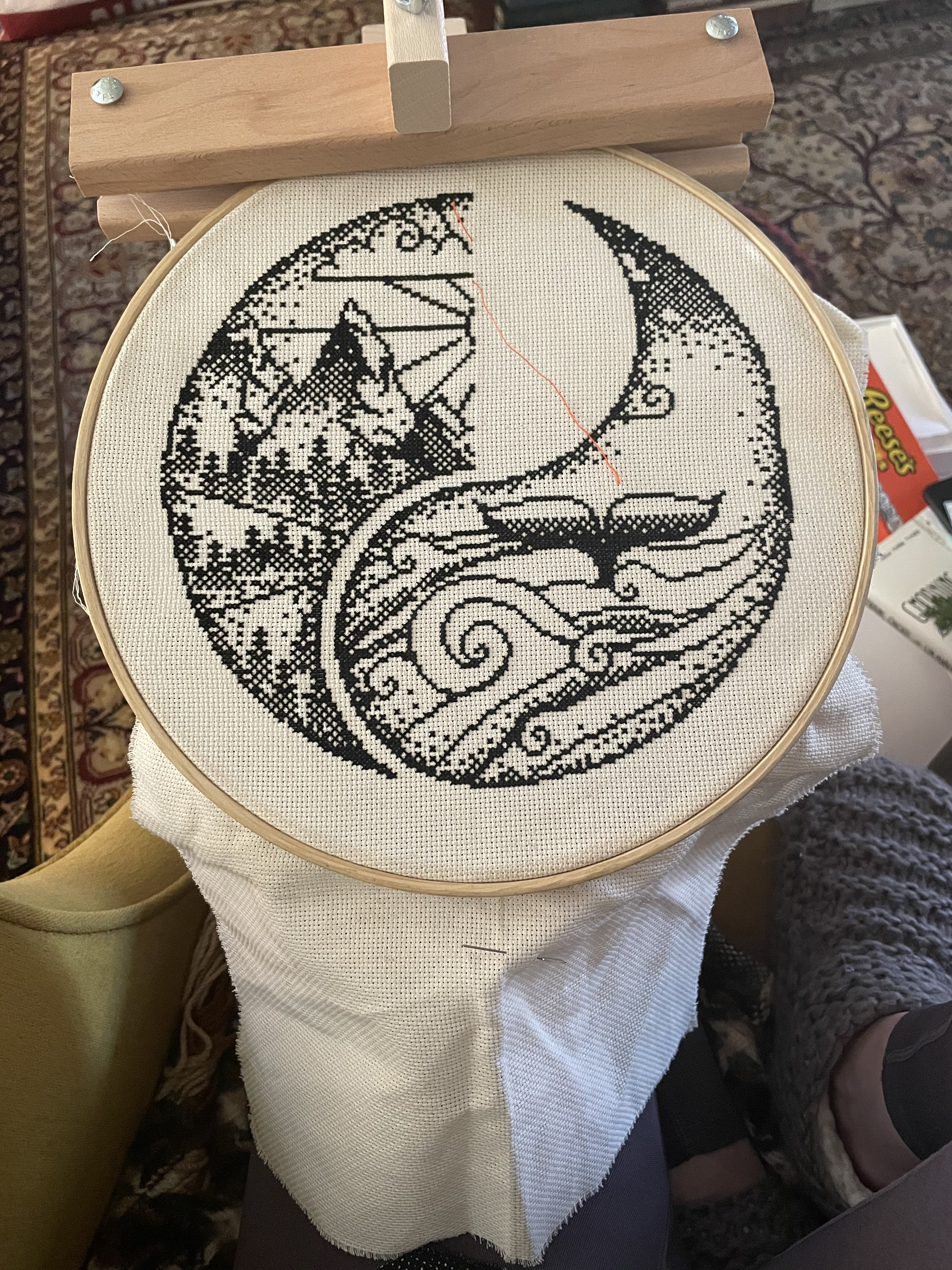 An image of a cross-stitch of the ocean and the mountains